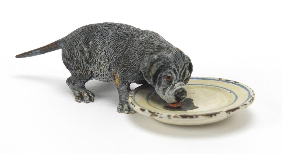 Austrian cold painted bronze dog licking a plate, stamped Geschutzt to the base, 9cm in length