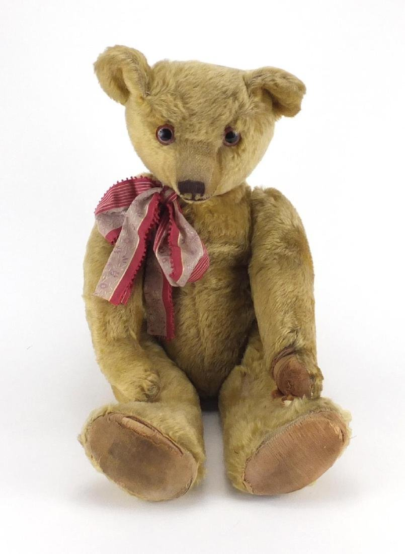 Vintage golden straw filled teddy bear with jointed limbs and beaded glass eyes, 63cm high Further