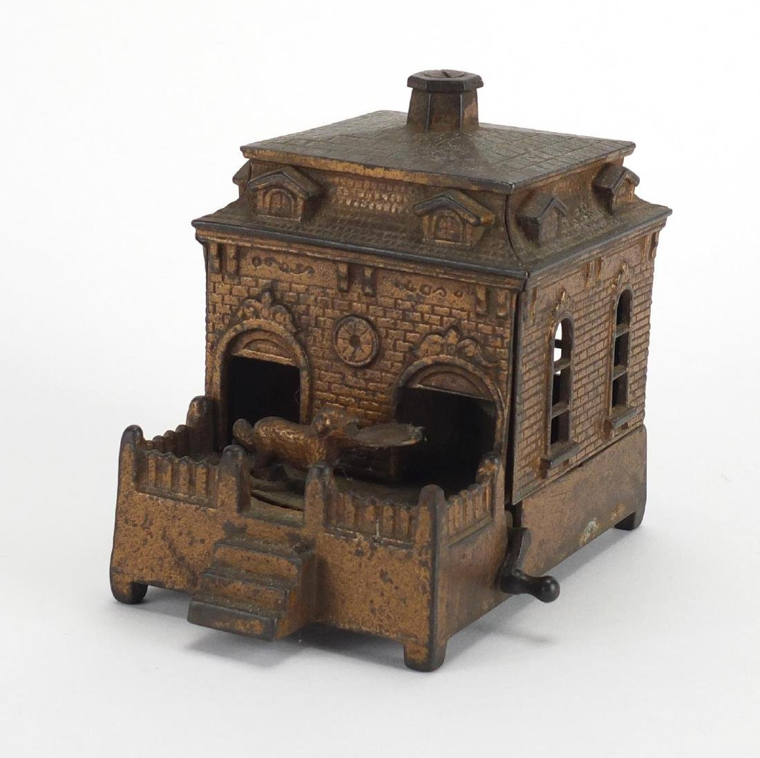 Novelty cast iron money box in the form of a dog rotating in and out of a house, 14cm in length