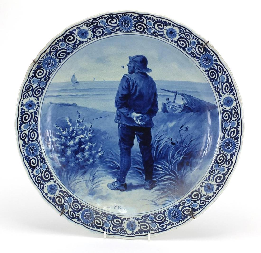 Delft blue and white pottery charger, hand painted with a sailor smoking a pipe within a floral