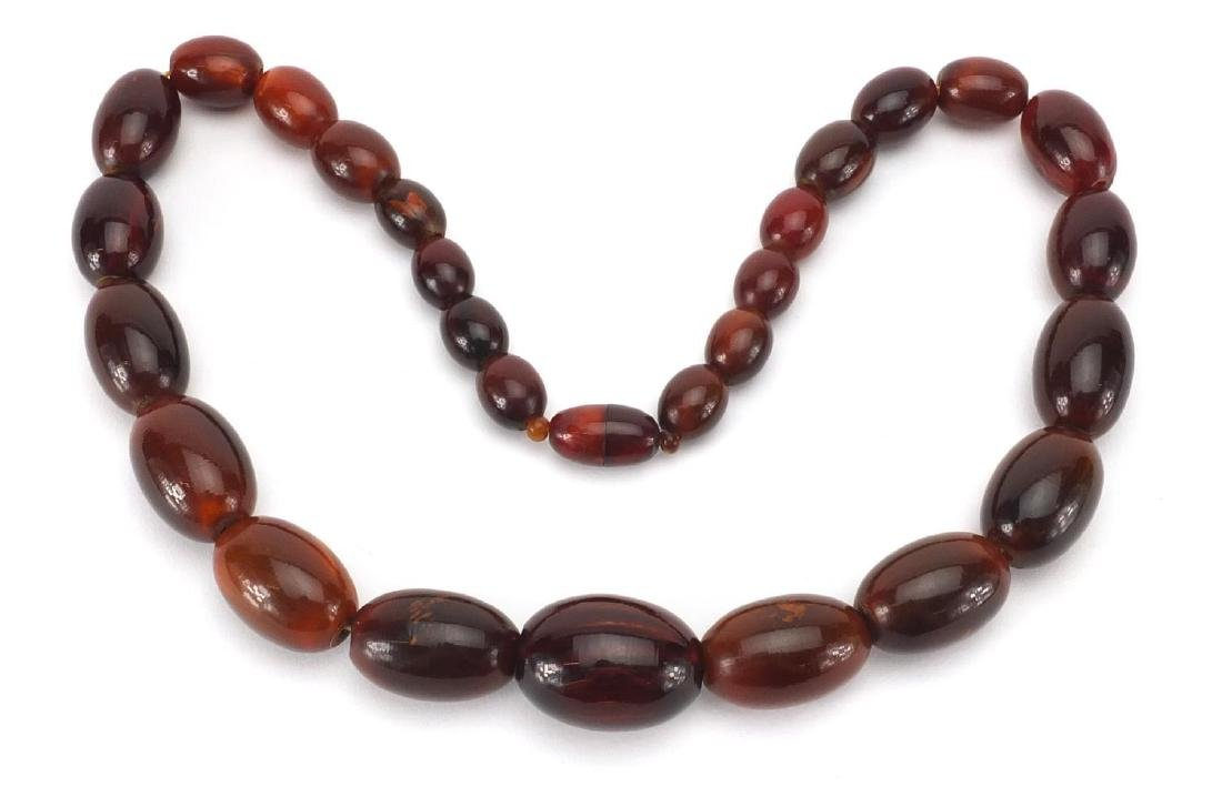 Horn bead necklace, possibly rhino horn, the largest bead 3.5cm wide, approximate weight 178g