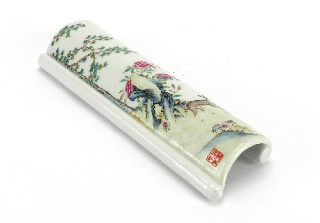 Chinese porcelain scholars wrist rest, hand painted in the famille rose palette with a dog