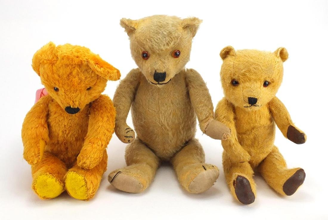 Three vintage teddy bear's including a straw filled example, all with jointed limbs and beaded eyes,
