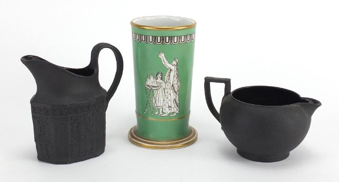 Two Victorian basalt milk jugs and a pottery spill vase decorated with a winged angel, the largest