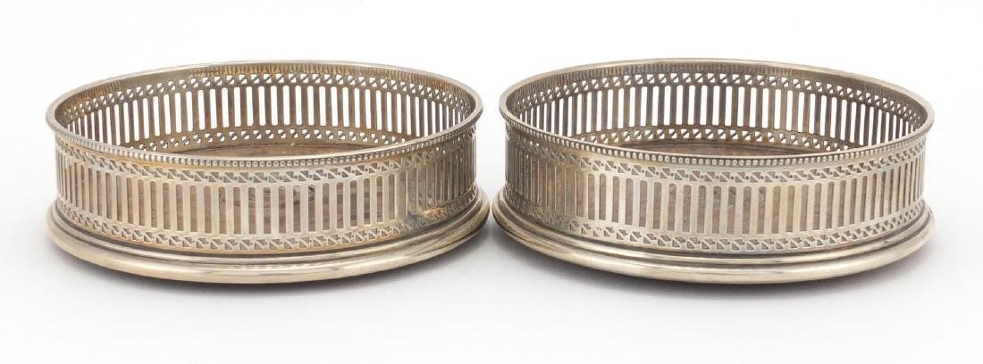 Pair of circular silver and oak wine coasters with pierced decoration, A C & S L D London 1979,