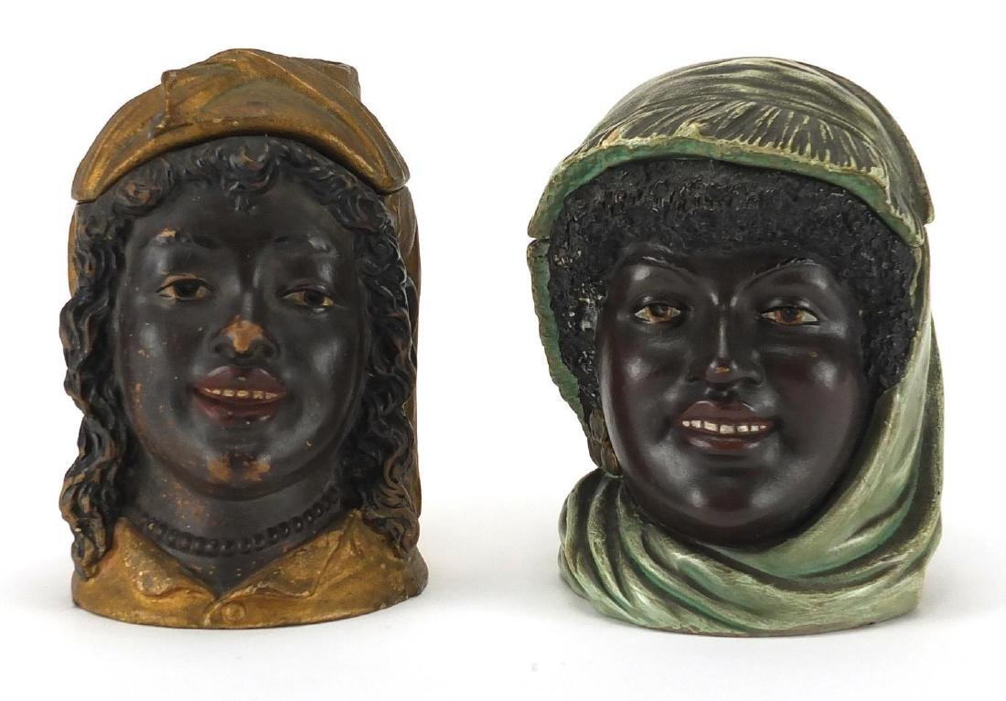 Pair of continental blackamoor tabacco jars and covers, both with impressed numbers to the bases,