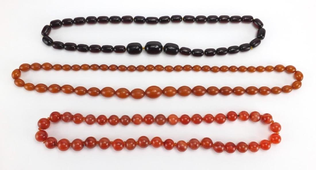 Two amber coloured bead necklaces and a cornelian bead necklace, the largest 80cm in length,