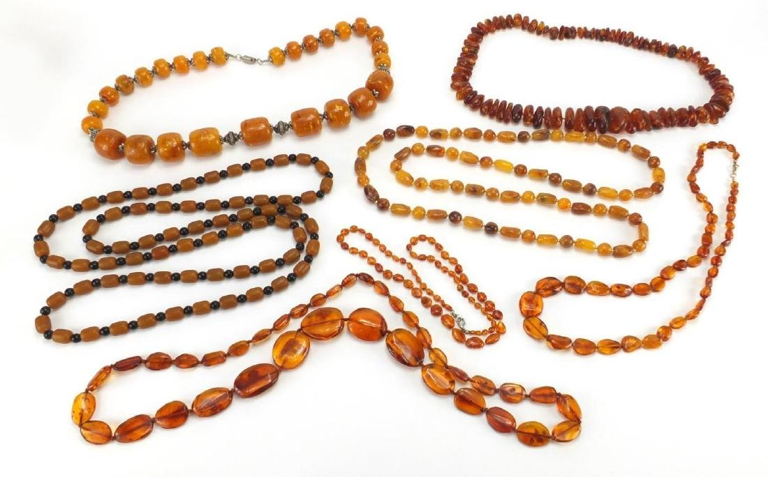Seven natural and butterscotch amber coloured bead necklaces, the largest 140cm in length,
