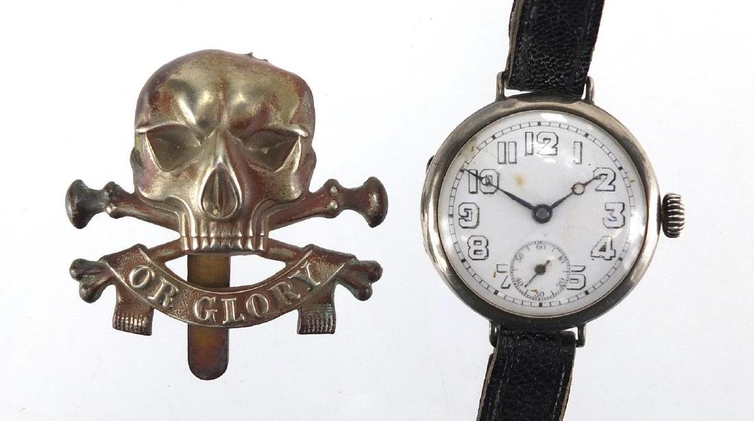 Military interest silver cased trench watch with enamelled dial and Roman numerals with cap badge