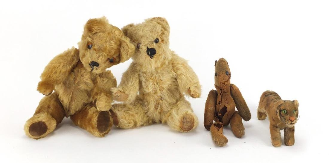 Two vintage straw filled teddy's with beaded eyes, straw filled tiger and one other, the largest