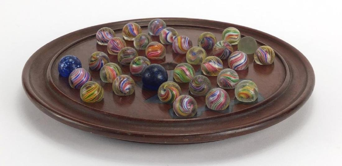 19th century solitaire board with marbles, the board 25.5cm in diameter Further condition reports