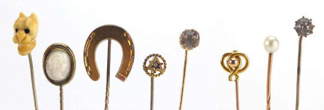 Eight vintage gold and gold coloured metal tie pins including a cameo, horse shoe and pearl