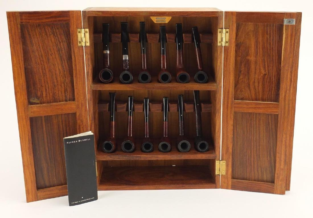 Twelve Dunhill smoking pipes housed in a hardwood pipe rack, including Shell Briar, Bruyere and Root
