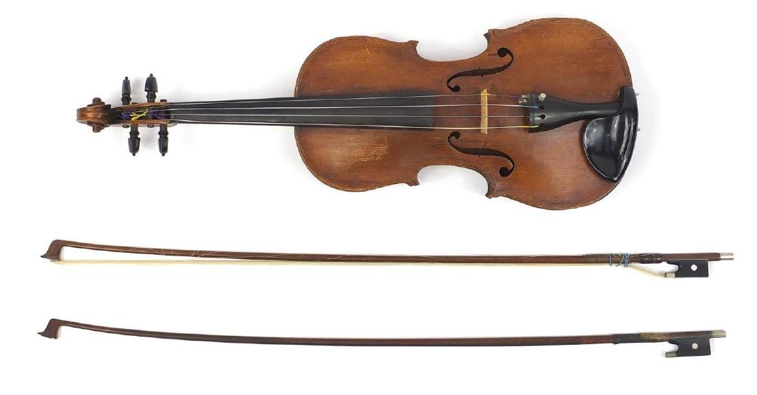 Old wooden violin with one piece back and scrolled neck, together with two unnamed violin bows and