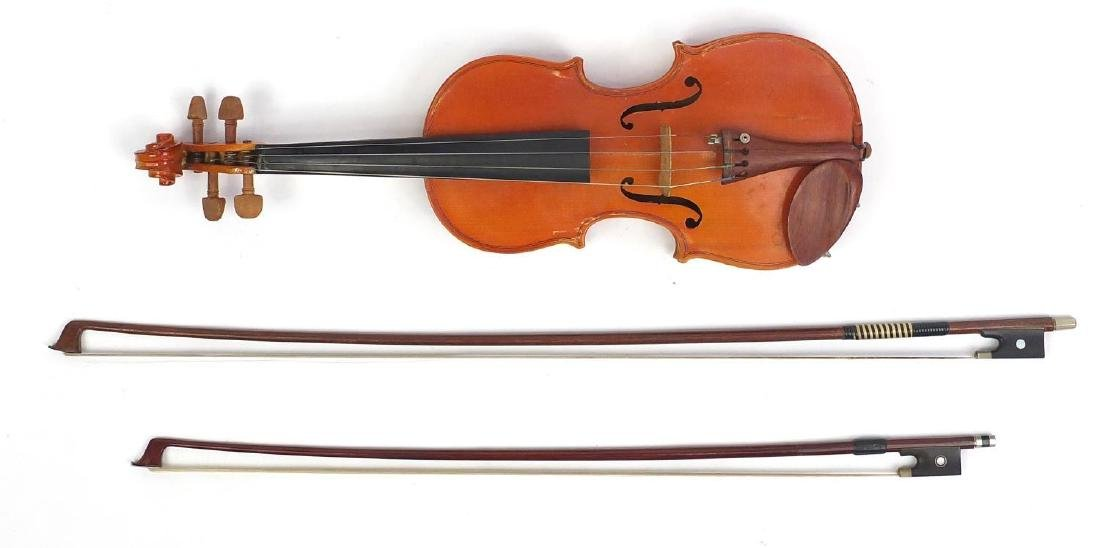 Old wooden violin with scrolled neck, two bows and fitted wooden carrying case, the violin bearing a