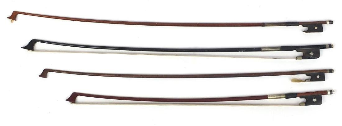 Four old wooden violin bows including an ebonised example each with Mother of Pearl frogs, one