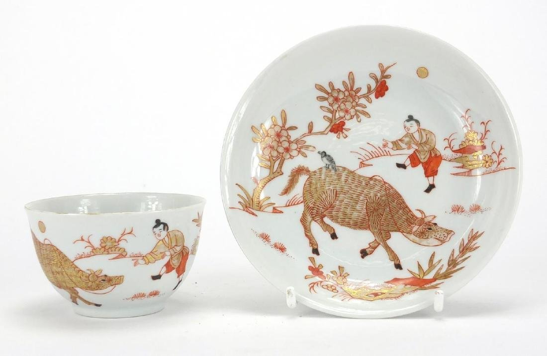 Chinese porcelain tea bowl and saucer, hand painted in iron red and gilded with a figure and water