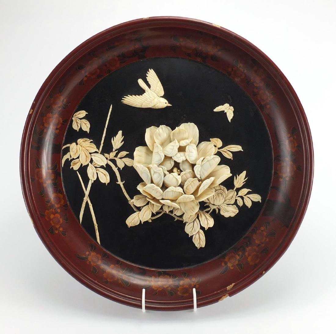 Chinese lacquered wall plaque with ivory inlay, decorated in relief with a blossoming flower, bird