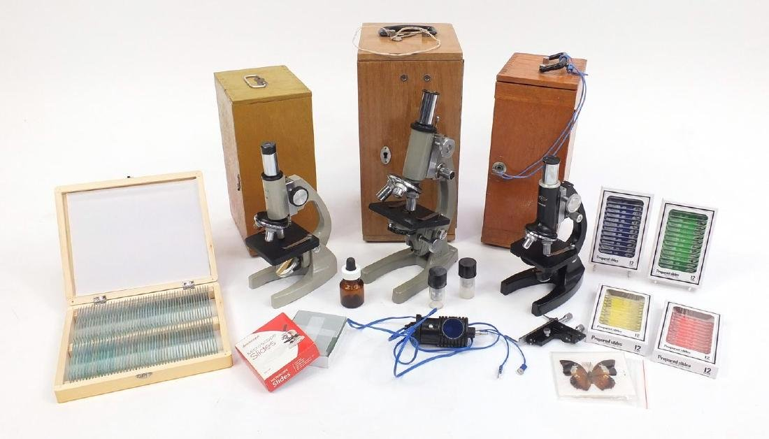 Three microscopes together with a collection of prepared slides, all with cases Further condition