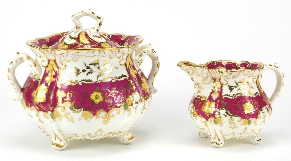 Victorian Rockingham creamer and lidded sucrier, each hand painted and gilded with flower heads
