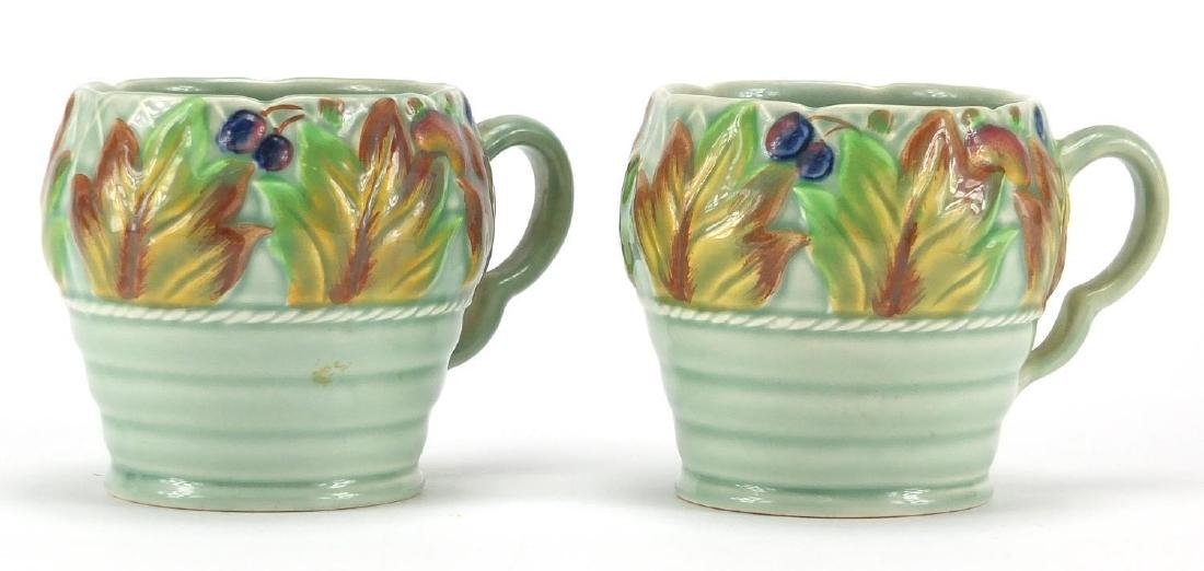 Pair of Clarice Cliff Newport pottery mugs, hand painted with berries and leaves, each numbered