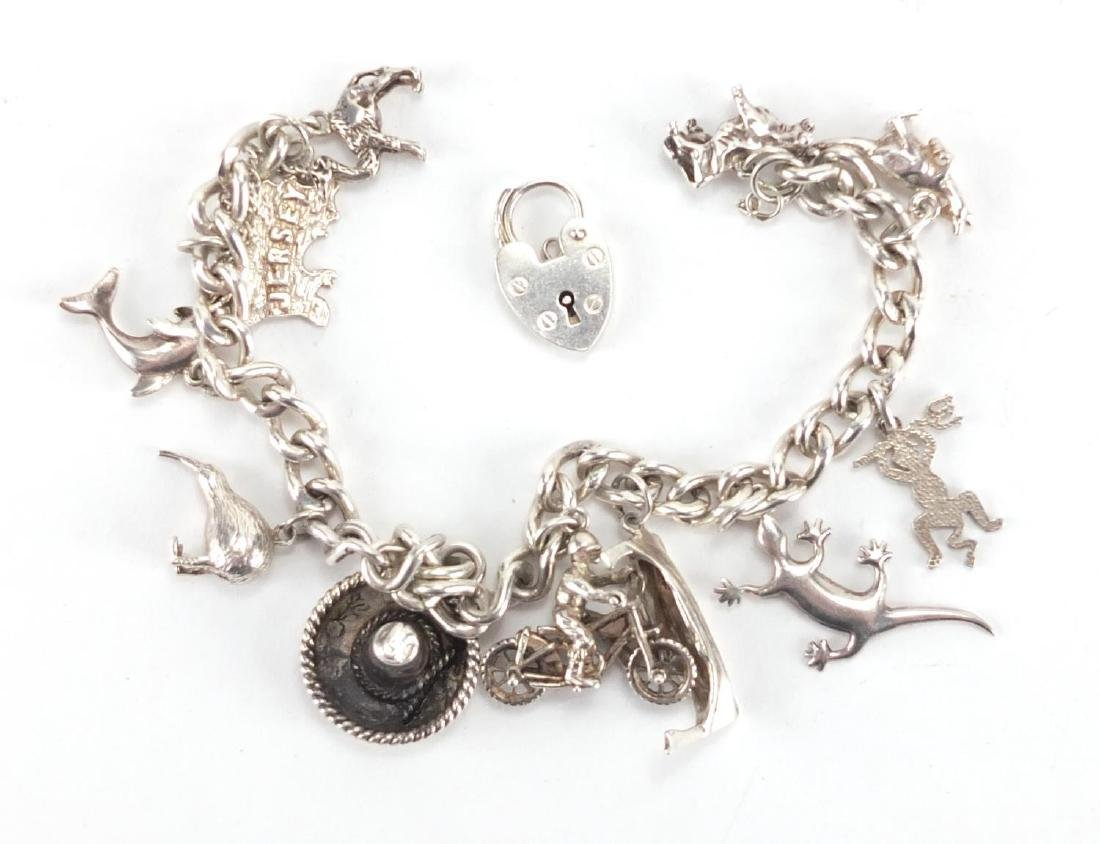Silver charm bracelet with a selection of charms including motorbike with rider and animals,