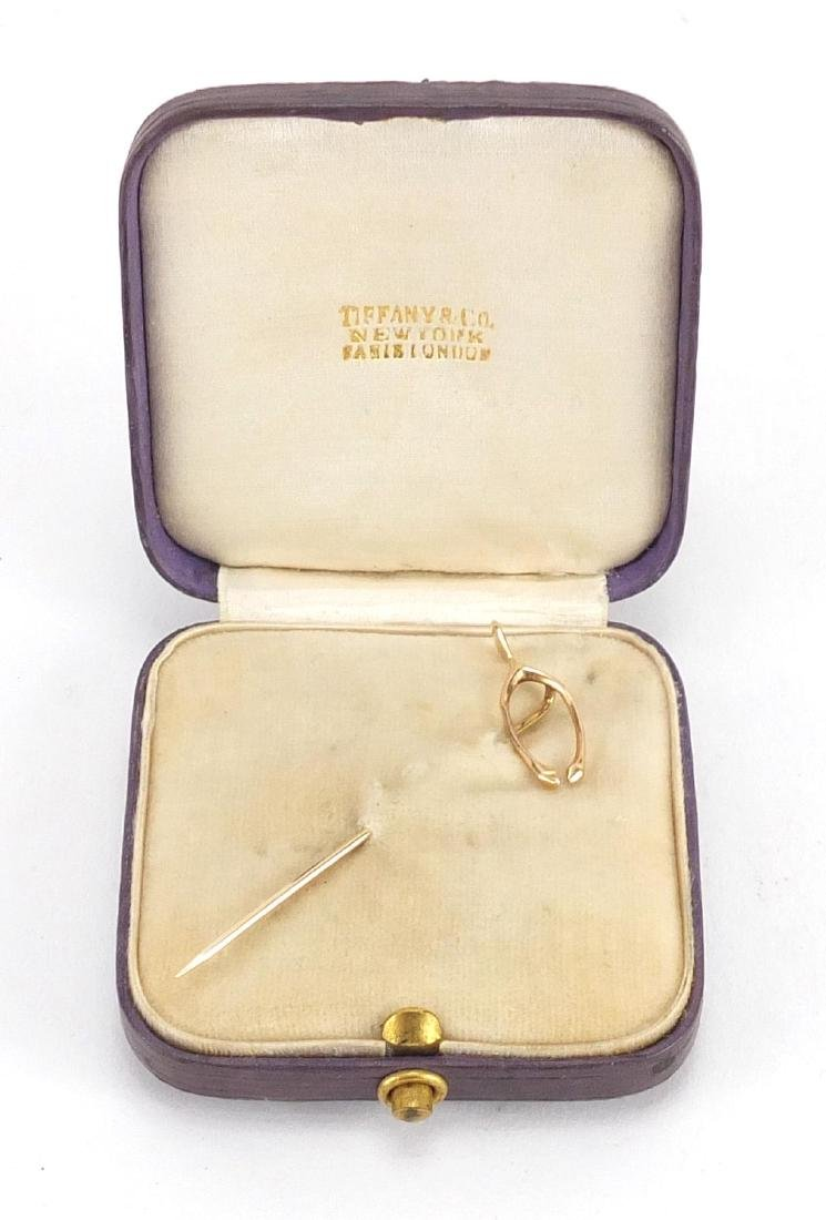 Unmarked gold wishbone tie pin, housed in a Tiffany & Co tooled leather box, the in 5cm in length,
