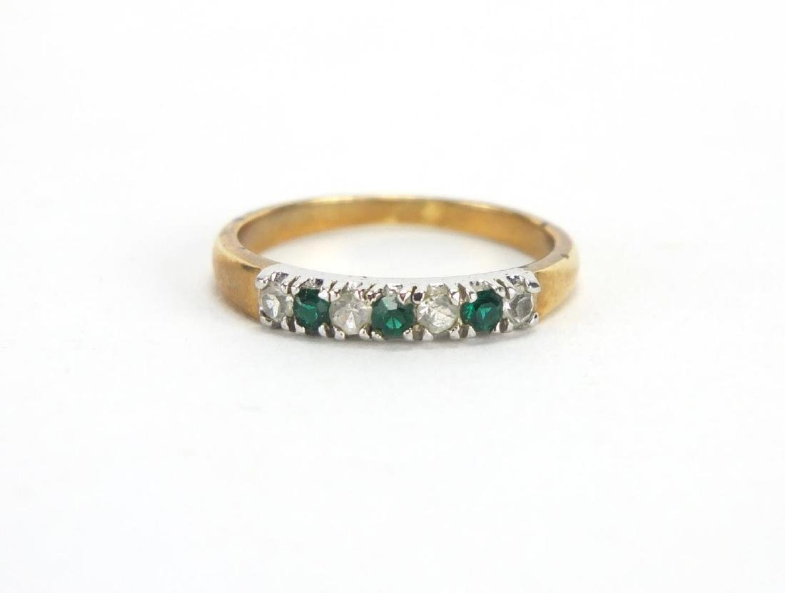 Gold coloured metal green and white stone half eternity ring, size P, approximate weight 2.1g :