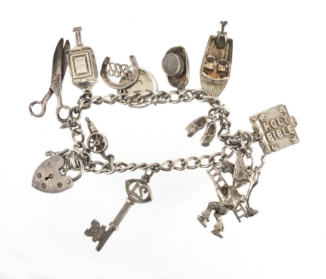 Silver charm bracelet with a selection of charms, including man with a ladder, speed boat,