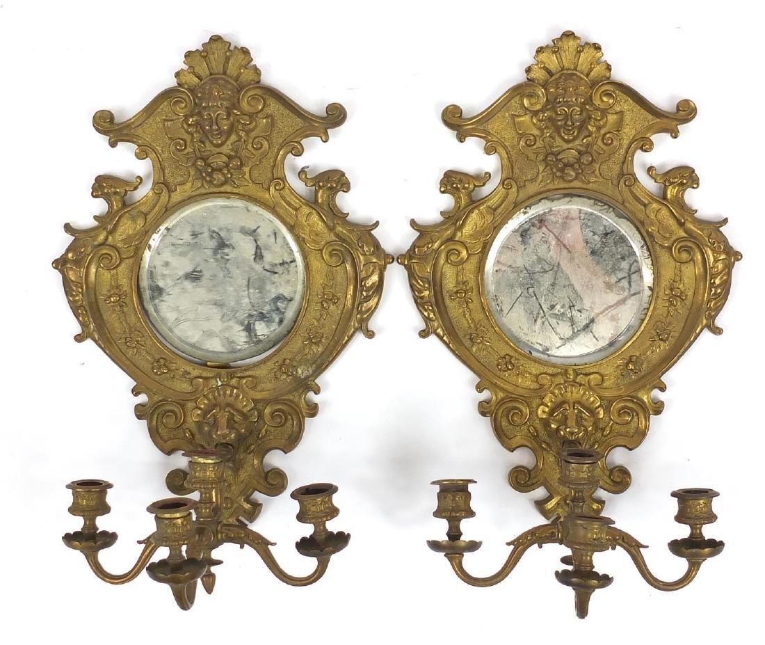 Pair of gilt brass Griffin design four branch wall sconces with circular bevelled mirrors, each 41cm