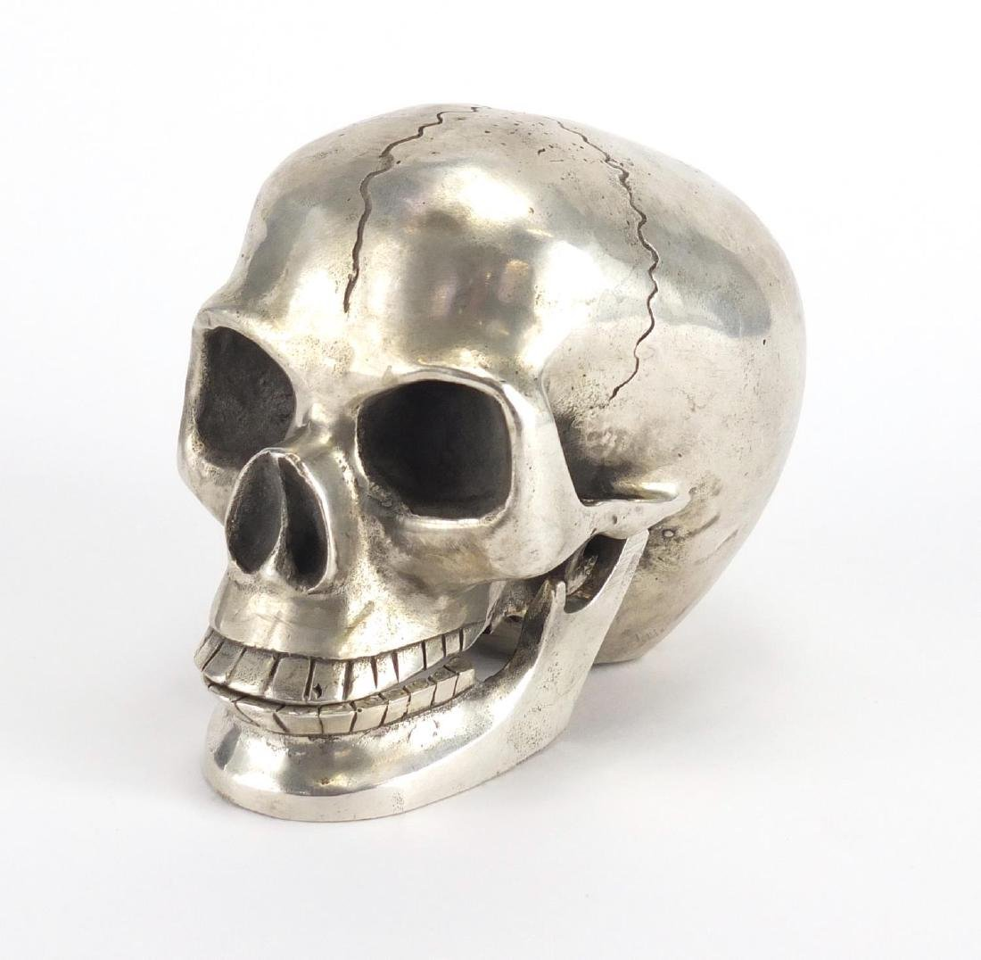 Silver coloured metal skull with articulated jaw, 10cm high