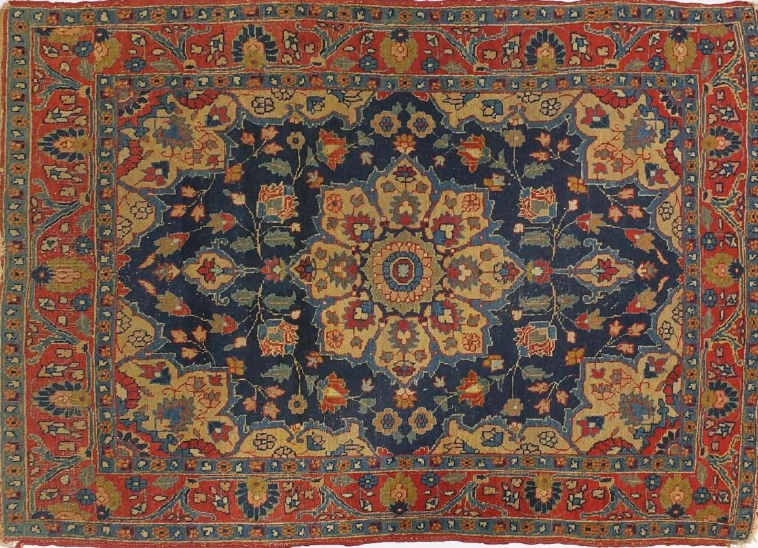 Rectangular Persian rug having a central flower head design surrounded by vines, onto and red and