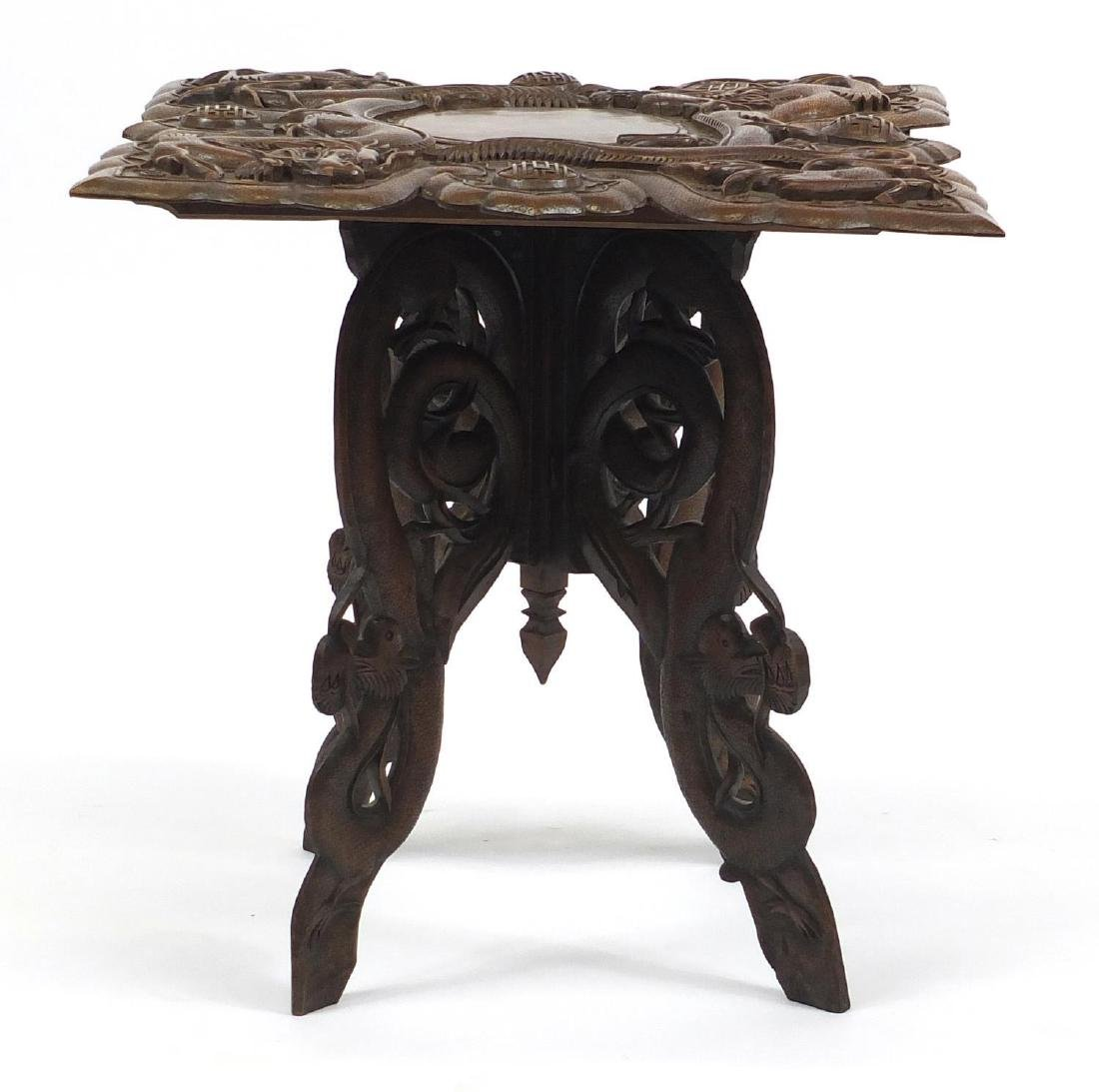 Chinese hardwood table, the square top deeply carved with two dragons, bats and symbols, 59cm H x