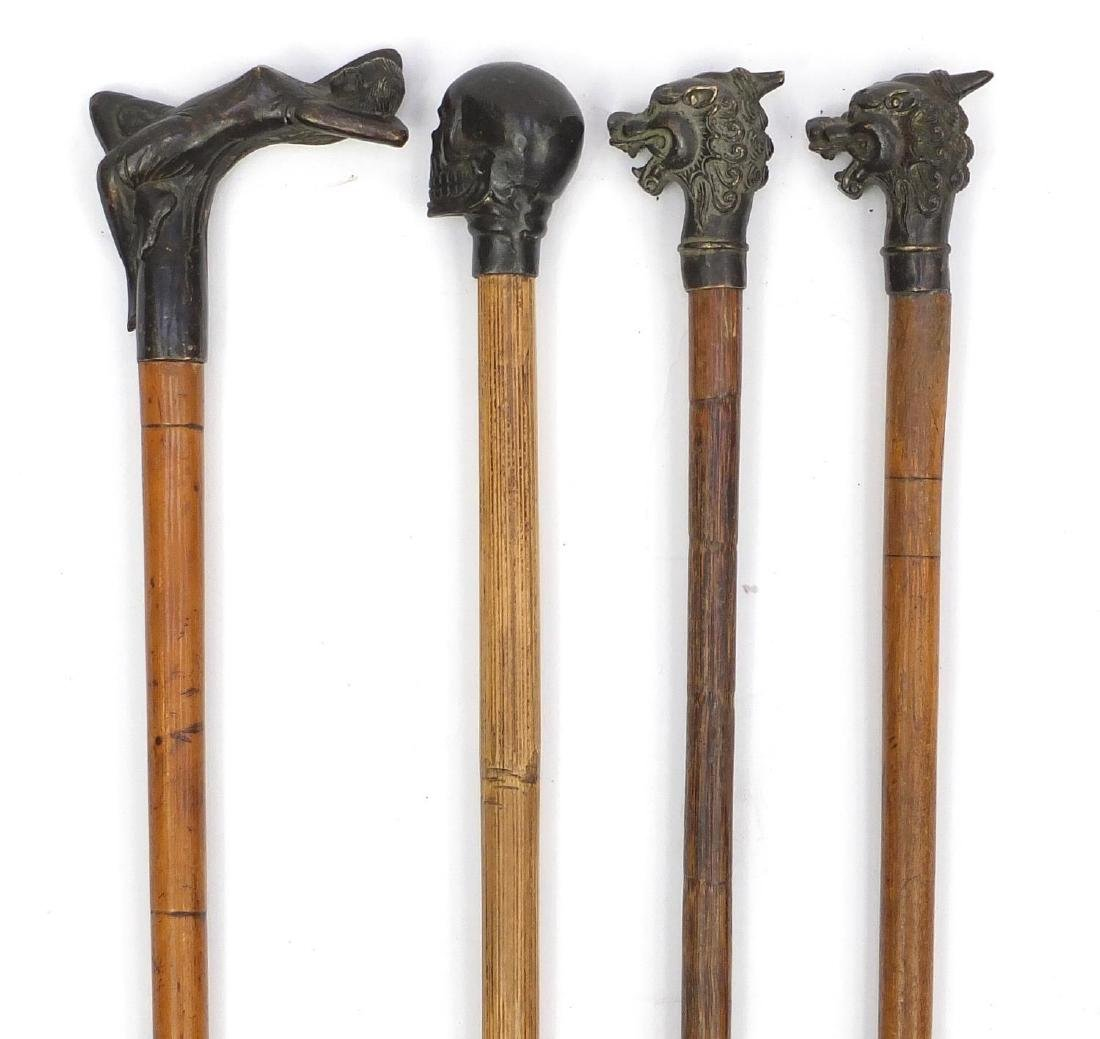 Four bronze topped walking sticks including one of a female and one of a skull, the largest 92cm