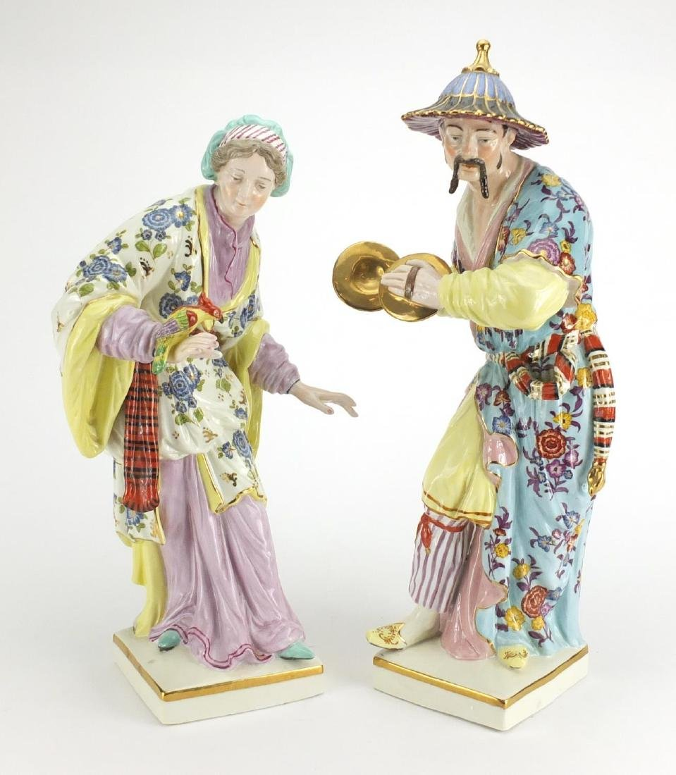 Large pair of Meissen style porcelain figures, each hand painted with flowers, both with crossword