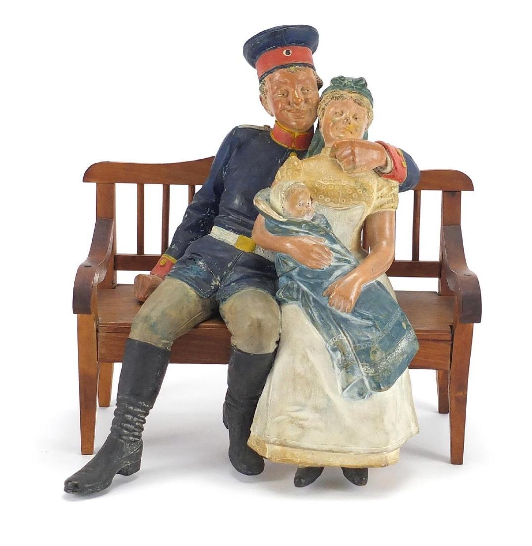 Continental hand painted terracotta family, seated on a bench, the bench 23.5cm high