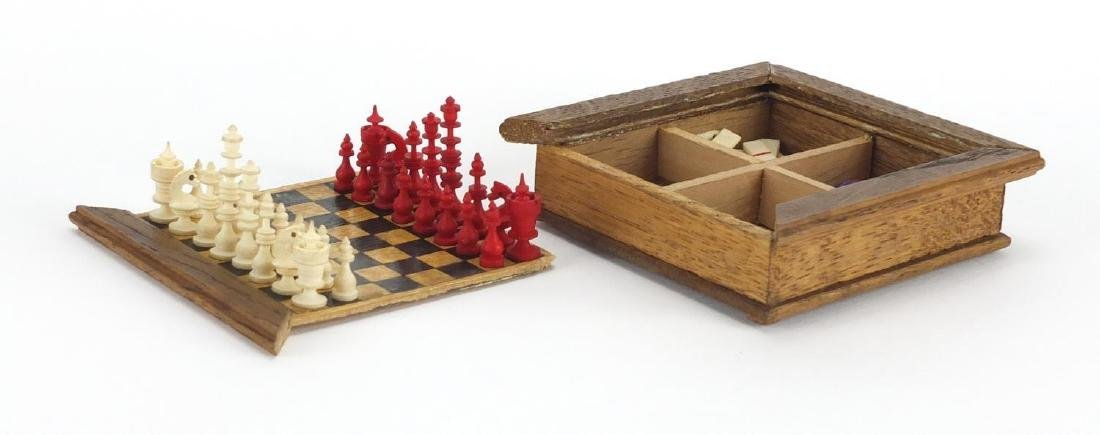 Miniature travelling games compendium, housing bone dominoes and bone chess pieces, the board 9cm