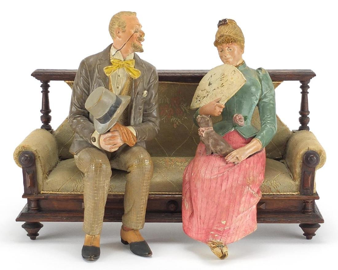Pair of continental hand painted terracotta lovers seated on a bench, the bench 30cm wide