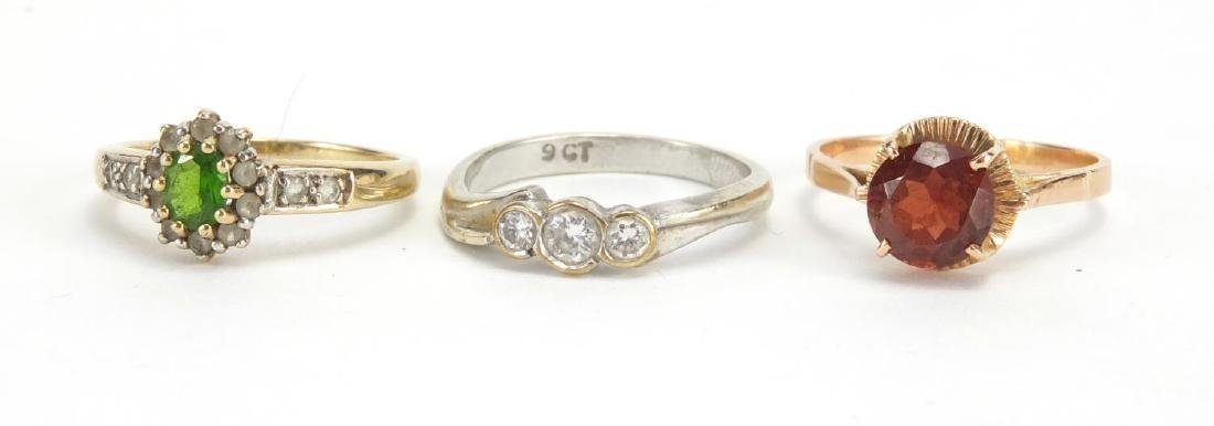 9ct gold green and clear stone ring, size N and two other rings set with assorted stones,