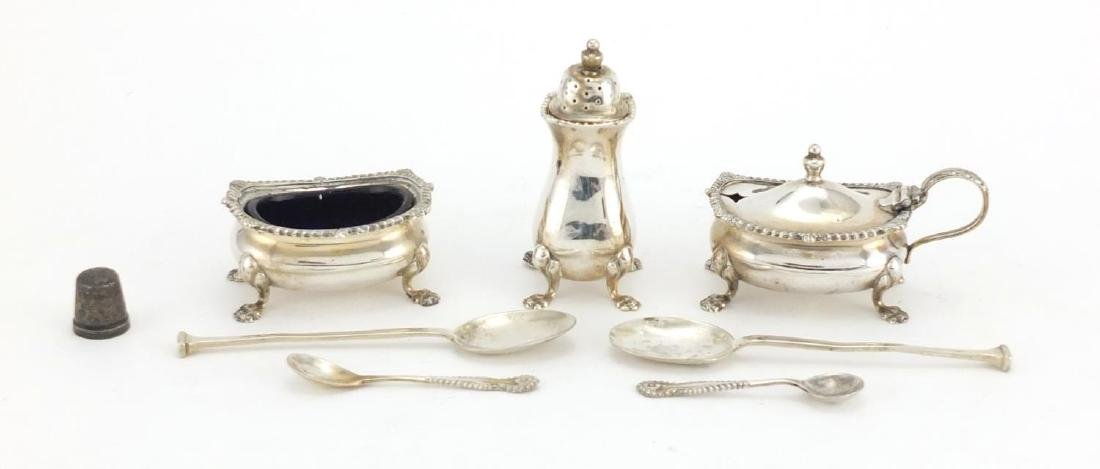 Silver three piece cruet, four silver spoons and a silver thimble, various hallmarks, the largest