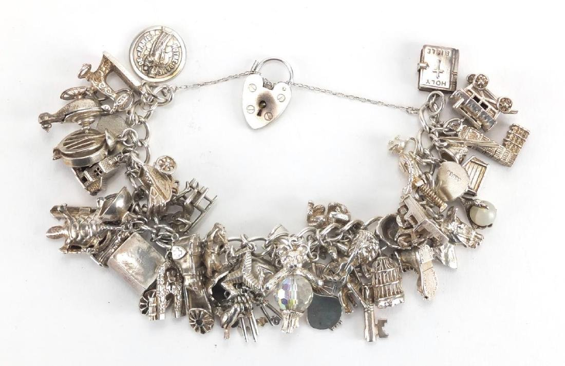 Heavy silver charm bracelet with a large selection of charms including a Genie lamp, vintage pram,