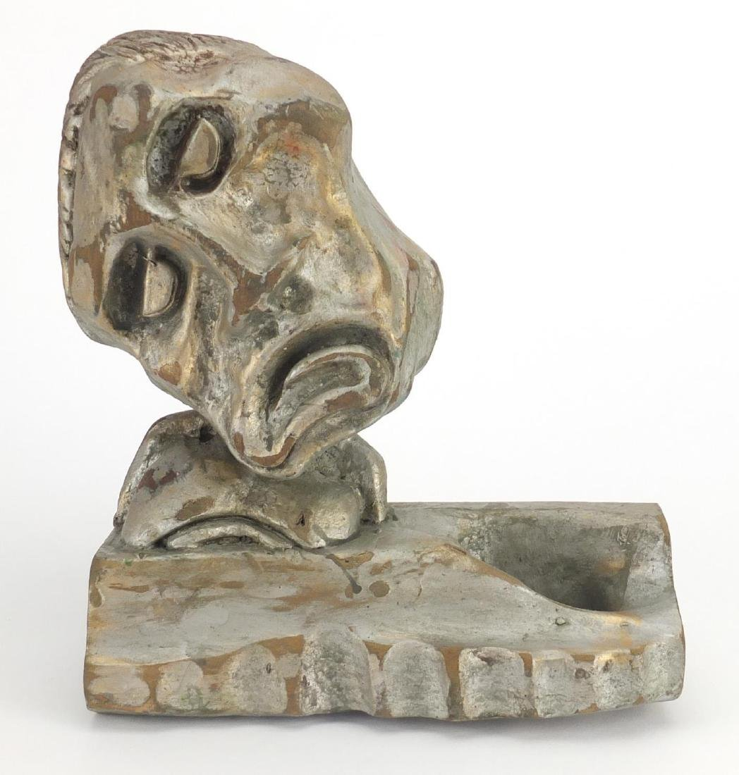 Silver painted carved wood sculpture of a grotesque face, carved Eric Gill to the reverse, 24cm high