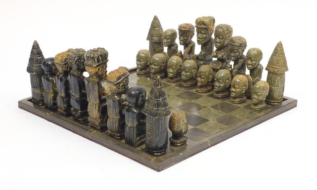 Green hard stone chess set of African design, the largest piece 14cm high