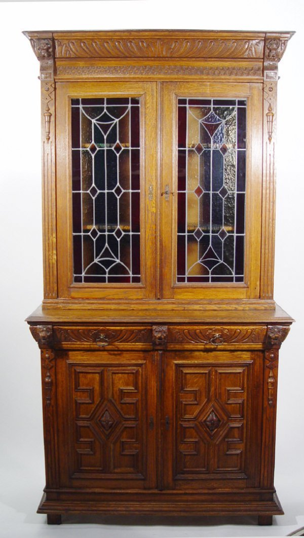 3: Heavily carved oak bookcase, the cornice flanked by