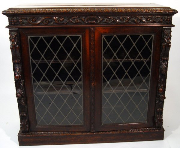 11: Oak bookcase heavily carved with masks, fruit and f