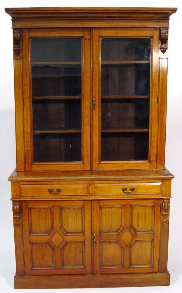 23: Victorian walnut bookcase, the moulded cornice abov