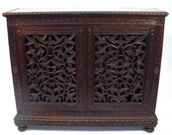 15: Hardwood bookcase with foliate carved frieze above