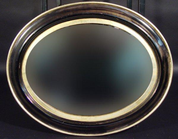 22: Irish oval bevel edged mirror in an ebonised and gi