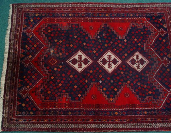 23: Rectangular red ground rug decorated with a blue an