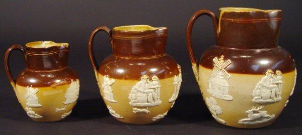 1204: Three graduated Royal Doulton stoneware jugs reli